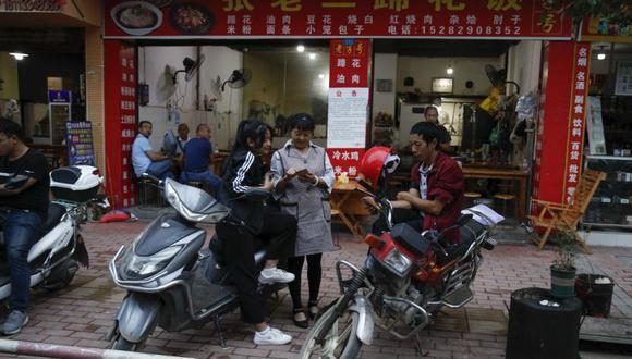 Las personas miran sus teléfonos inteligentes en motocicletas estacionadas cerca de un restaurante en el condado de Ganluo, provincia de Sichuan, suroeste de China. (Foto: AP / Andy Wong).