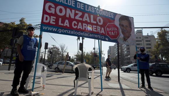 Dos hombres sujetan un cartel de propaganda en una calle de Santiago de Chile. El país dio este miércoles el pistoletazo de salida a la campaña electoral para los megacomicios municipales, regionales y constituyentes de los próximos 15 y 16 de mayo, en momentos en que la pandemia se estabilizada tras una grave segunda ola. EFE/Alberto Valdés