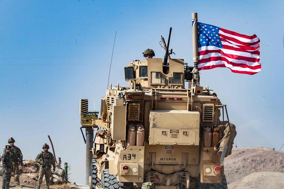 Soldados estadounidenses cerca de una manifestación de kurdos sirios contra las amenazas turcas en una base de coalición internacional en las afueras de la ciudad de Ras al-Ain, en la provincia siria de Hasakeh. (AFP / Delil SOULEIMAN).
