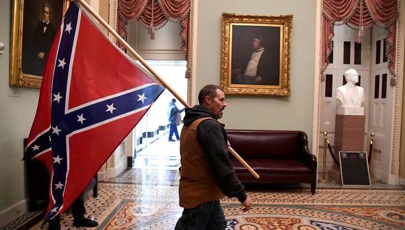 Un seguidor de Trump camina dentro del Congreso estadounidense con la bandera confederada, aquella que enarbolaban los esclavistas en la guerra civil. REUTERS/Mike Theiler