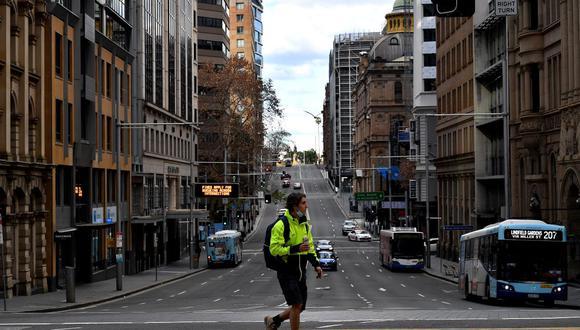 Esta imagen tomada el 26 de junio de 2021 muestra a un hombre caminando por las tranquilas calles de Sídney durante un nuevo confinamiento por coronavirus. (Saeed KHAN / AFP).