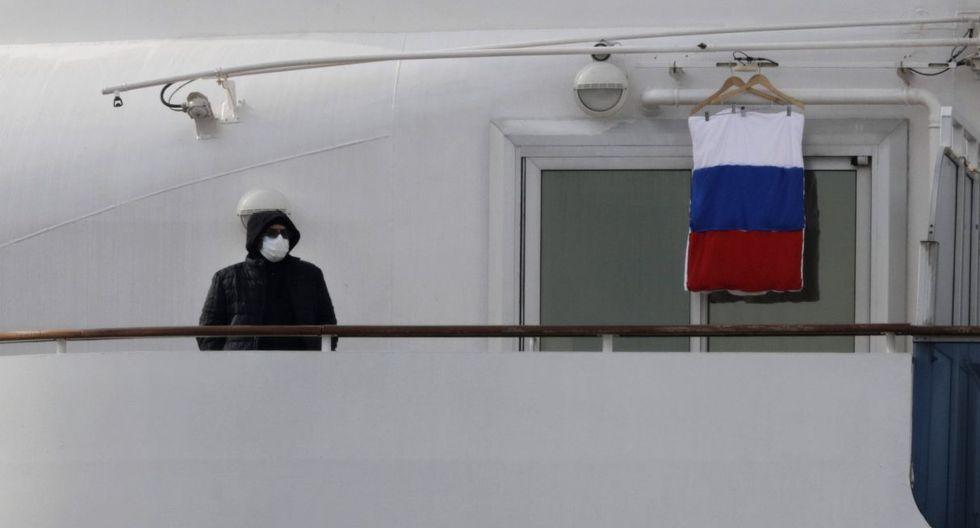 Un pasajero en cuarentena en el crucero Diamond Princess es visto en su balcón junto a una bandera de Rusia. (AP).
