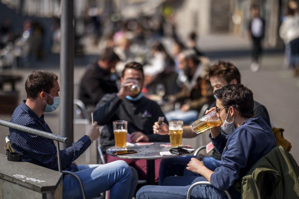 """La gente disfruta de una cerveza y juega a las cartas cuando las terrazas de bares reabrieron en Lausana, el 19 de abril de 2021, luego de que el Gobierno de Suiza aliviara significativamente sus restricciones de COVID-19 a pesar de reconocer que la situación del virus del país """"sigue siendo frágil"""" e incluso ha empeorado recientemente. (Foto de Valentín FLAURAUD / AFP)"""