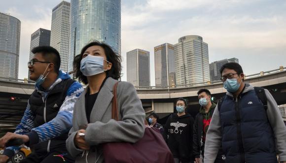 Mujeres que usan mascarillas para protegerse contra el coronavirus cruzan una intersección en el distrito comercial central de Beijing. (Foto: AP / Mark Schiefelbein).