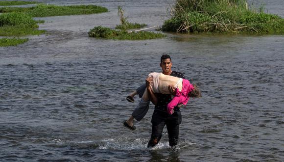 Un muchacho venezolano carga a una mujer de la tercera edad para ayudarla a atravesar el Río Grande, en la frontera de México y Estados Unidos. REUTERS