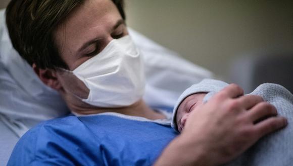 Un padre con máscara protectora sostiene a su hijo recién nacido contra su pecho durante la pandemia de coronavirus en París, Francia, el 17 de noviembre de 2020. (Martin BUREAU / AFP).