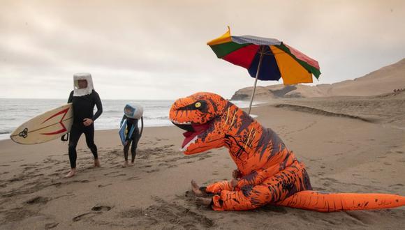EXTINCIÓN PLAYERA. El amenazante dinosaurio (Jhan Suclupe) es casi una metáfora de lo que podría ser este verano, con balnearios rodeados de agentes policiales, bañistas multados y, lo que es peor, un rebrote seguro. (Foto: Luis Miranda)