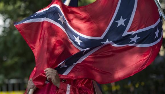 En esta foto de archivo tomada el 8 de julio de 2017, un miembro del Ku Klux Klan sostiene una bandera confederada. (Foto: ANDREW CABALLERO-REYNOLDS / AFP ).