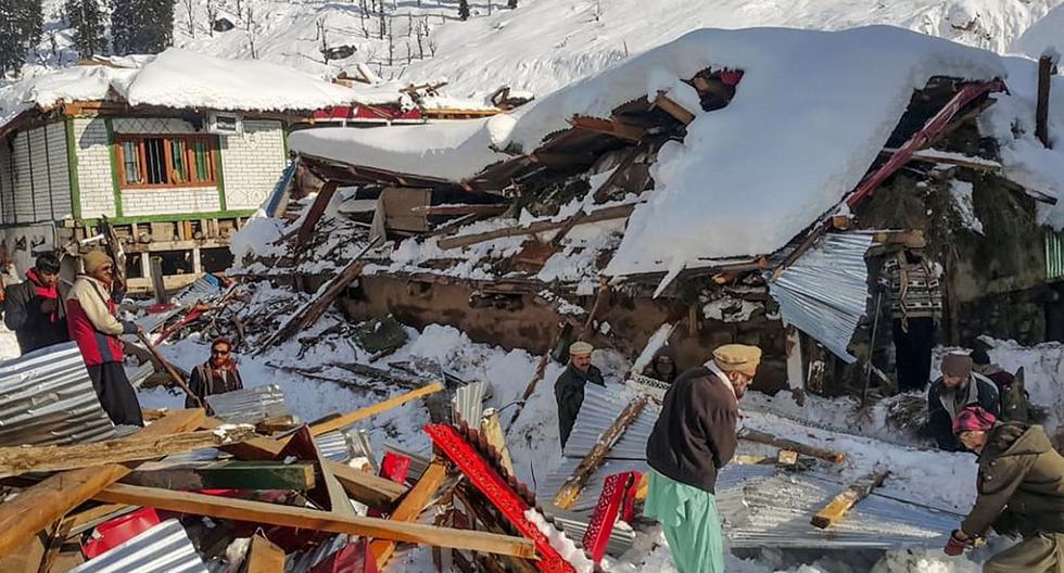 Un grupo de residentes locales retiran los escombros de una casa derrumbada después de una fuerte nevada que desencadenó una avalancha en el valle de Neelum, en Cachemira. (AFP)