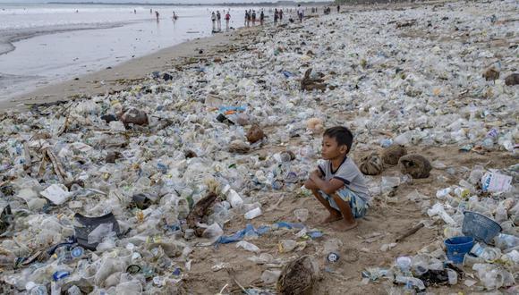 En la foto, un niño se sienta en la playa cubierta de desechos plásticos en la playa de Kuta en Bali, Indonesia, el 31 de diciembre de 2020. Para evitar situaciones como esta es importante fomentar la educación ambiental. (Foto de archivo: EFE)