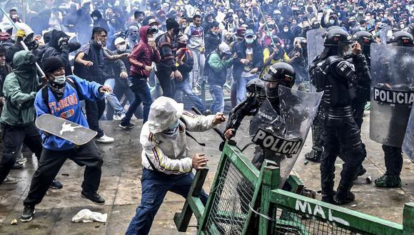 Manifestantes chocan con la policía antidisturbios durante una protesta contra un proyecto de reforma tributaria lanzado por el presidente colombiano Iván Duque, en Bogotá, el 28 de abril de 2021. (Juan BARRETO / AFP).