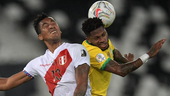 El volante peruano Renato Tapia salta con el brasileño Fred para ganar un balón en el juego aéreo durante el Perú vs. Brasil por la semifinal de la Copa América 2021. (Foto: AFP)