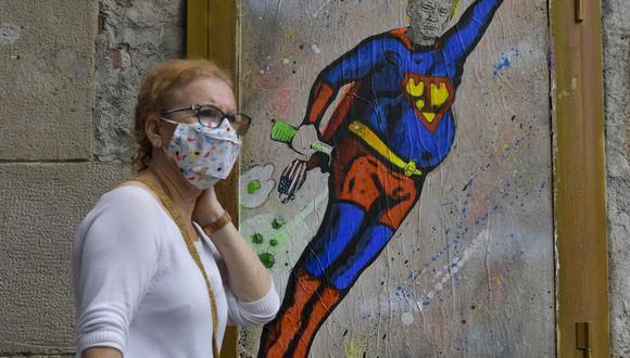 Una mujer pasa junto a una nueva obra de arte del artista callejero TVBoy que representa al presidente de Estados Unidos, Donald Trump, vestido con un disfraz de Superman y volando a través de las nubes COVID-19 en Barcelona el 8 de octubre de 2020 (Foto: Pau BARRENA / AFP).