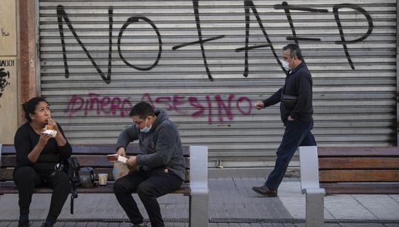 Un hombre pasa por un grafiti contra la Administración de Fondos de Pensiones (AFP) en Santiago de Chile (Chile), el 15 de julio de 2020. (MARTIN BERNETTI / AFP).