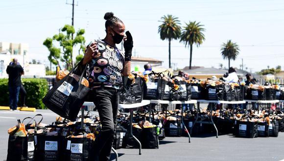 Una mujer ajusta su mascarilla en plena repartición de comida en Los Ángeles. (Fuente: AFP)