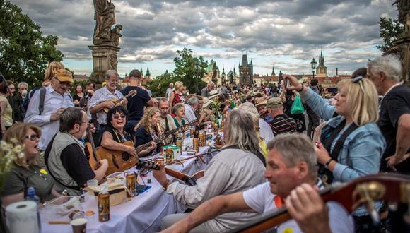 Coronavirus | Los músicos interactúan con los comensales  en el emblemático Puente de Carlos en Praga, República Checa. (EFE / EPA / MARTIN DIVISEK).
