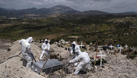 Trabajadores de un cementerio entierran a una víctima del coronavirus COVID-19 no reclamada en Tijuana, estado de Baja California, México. (Guillermo Arias / AFP).