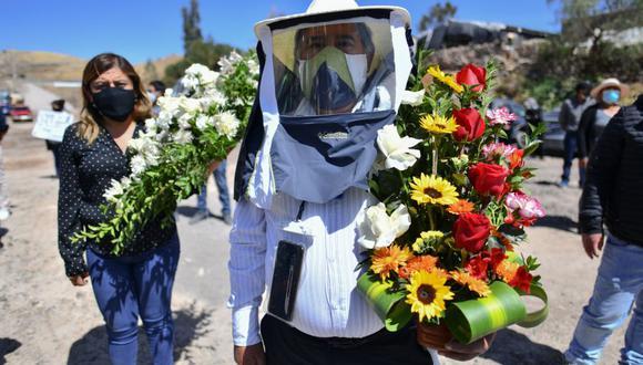 Habitantes de la comunidad rural de Yura, cercana a la ciudad de Arequipa, en el sur de Perú, participan en el entierro de su alcalde Angel Benavente, con una misa al aire libre y una posesión fúnebre. La autoridad murió de coronavirus. (Foto: Diego Ramos / AFP).