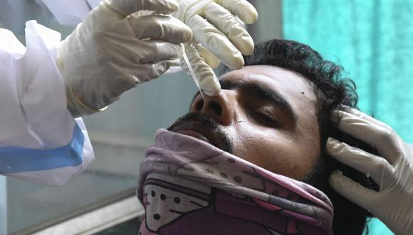 Un trabajador de la salud toma una muestra de un hisopo nasal a un hombre para realizar la prueba del coronavirus Covid-19 en Amritsar, India, el 21 de abril de 2021. (Foto de NARINDER NANU / AFP).