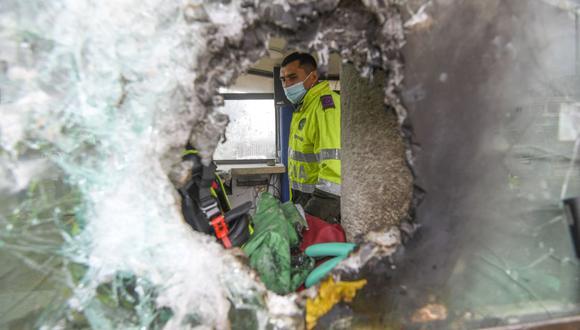 Policías inspeccionan daños causados por manifestantes en una comisaría de Bogotá el 5 de mayo de 2021. (Foto de Juan BARRETO / AFP).