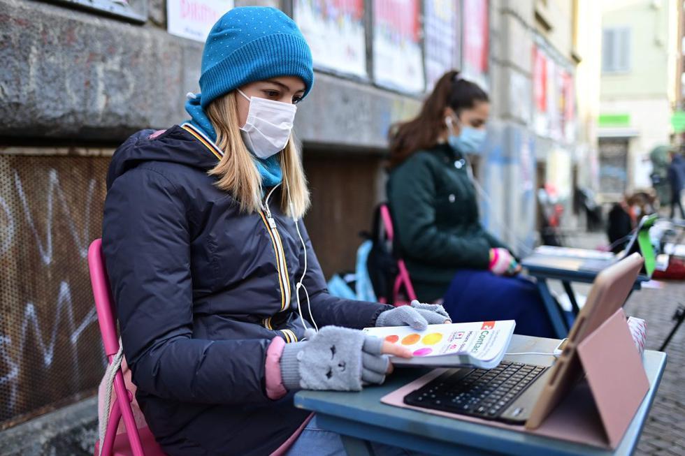 Anita Iacovelli (izquierda) y su amiga Lisa Rogliatti, ambas de 12 años, se sientan frente a la escuela Italo Calvino en medio de la pandemia de coronavirus en Turín (Italia). (AFP / Miguel MEDINA).