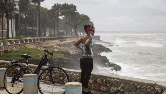 Una mujer observa el fuerte oleaje durante el paso de la tormenta Elsa en el Malecón de Santo Domingo, república Dominicana, el 3 de julio de 2021. (Foto de Erika SANTELICES / AFP).