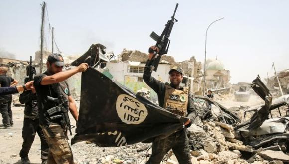 Soldados iraquíes en Mosul levantan una gran bandera negra del grupo yihadista en la mano, al revés como símbolo de derrota. (Foto: AFP)