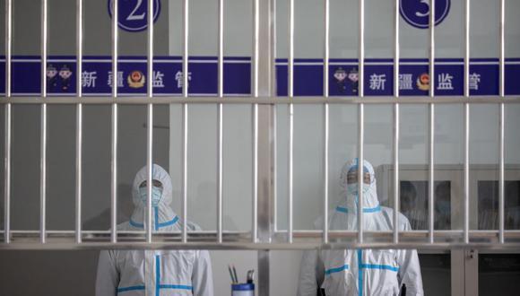 Agentes de seguridad con trajes protectores se encuentran en un área de recepción en la sala de visitantes del centro de detención Urumqi No. 3 en Dabancheng, en la Región Autónoma Uigur de Xinjiang, en el oeste de China. (Foto: AP / Mark Schiefelbein)