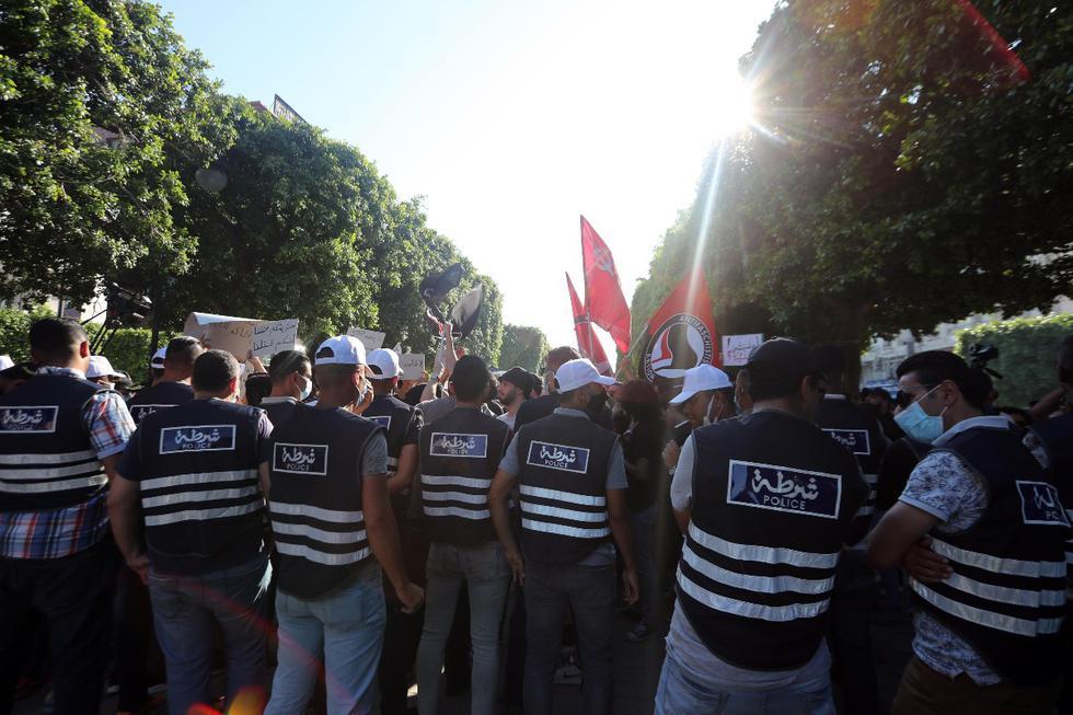 Las fuerzas policiales se reúnen mientras manifestantes tunecinos contra el gobierno gritan consignas durante una protesta contra la violencia policial en Túnez. La gente organizó una manifestación para protestar por la muerte de un joven , quien presuntamente murió luego de ser golpeado por agentes del orden mientras estaba bajo custodia. (Foto: EFE)
