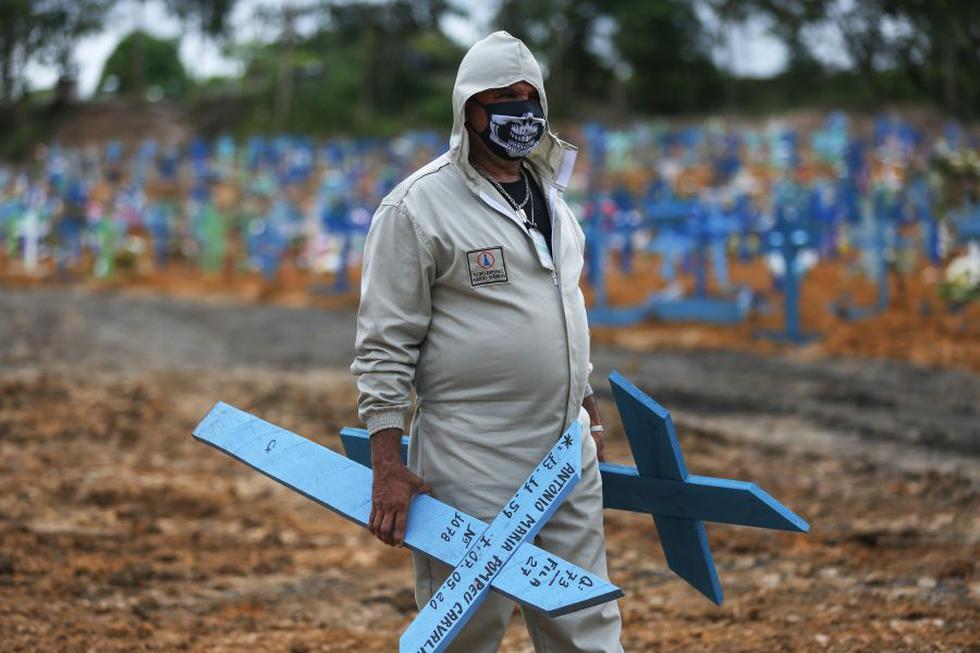 El brasileño Ulisses Xavier, de 52 años, que ha trabajado durante 16 años en el cementerio de Nossa Senhora en Manaus, Brasil, se prepara para colocar cruces en las tumbas durante su turno del 8 de mayo de 2020, en medio de la nueva pandemia de coronavirus. (MICHAEL DANTAS / AFP).