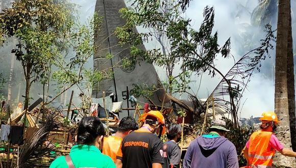 Los rescatistas llegan mientras el humo sale de los restos de un avión de transporte C-130 de la Fuerza Aérea de Filipinas después de que se estrellara cerca del aeropuerto en la ciudad de Jolo. (Foto: AFP).