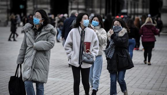 Un grupo de turistas camina usando mascarillas protectoras en medio del temor a la propagación del coronavirus COVID-19 en París. (AFP)