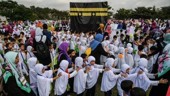Niños malasios circulan una maqueta de la Kaaba, la estructura más sagrada del Islam ubicada en la ciudad santa de La Meca. (Foto referencial: AFP)