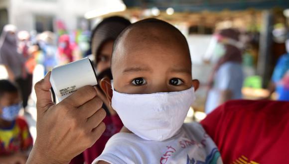 Toman la temperatura de un niño en Tailandia en medio de la pandemia del coronavirus, el 17 de abril de 2020.  Foto: AFP / Madaree TOHLALA