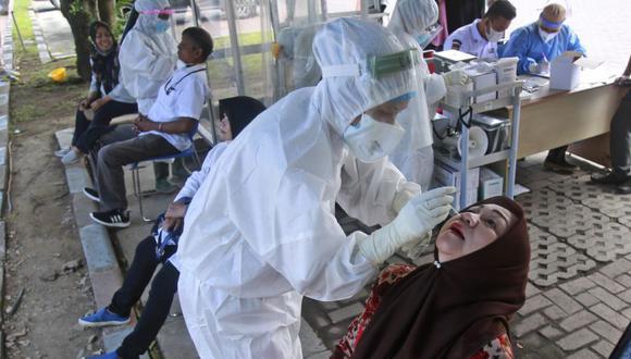 Trabajadores médicos recogen muestras de hisopos nasales de una mujer para realizar la prueba de coronavirus durante una prueba de detección de COVID-19 en la Universidad de Sumatra del Norte en Medan, Indonesia.(Foto; AP/Binsar Bakkara)