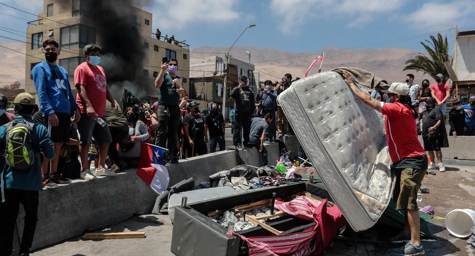 Grupo de personas queman carpas que eran utilizadas por extranjeros para pernoctar en plazas y playas en Iquique, Chile. (EFE/ Johan Berna).