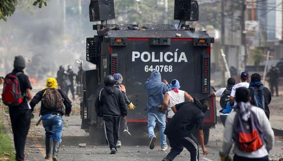 Manifestantes arrojan piedras a un vehículo policial durante una protesta contra el gobierno en Popayán, Cauca, Colombia, el 14 de mayo de 2021. (Julián MORENO / AFP).