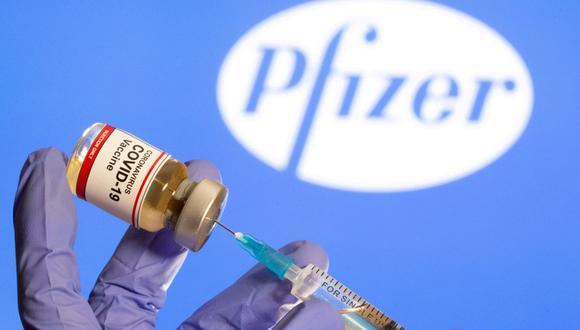 """Una mujer sostiene una pequeña botella con una etiqueta de """"Vacuna contra el coronavirus COVID-19"""" y una jeringa médica frente al logotipo de Pfizer. (REUTERS/Dado Ruvic)."""