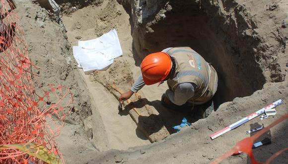 Obrero limpiando con una brocha la osamenta que encontraron durante los trabajos para instalar la red de gas natural en la calle Atahualpa. (Foto: Laura Urbina)