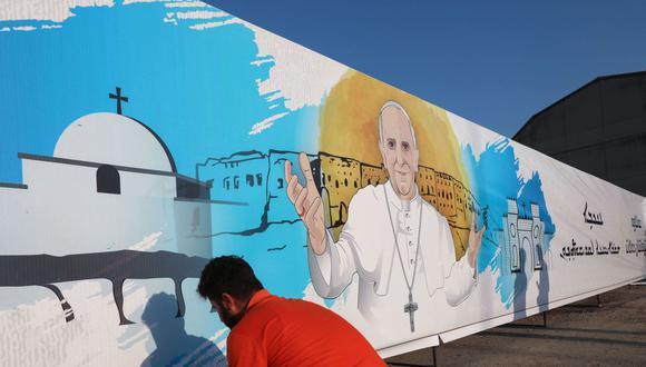 Un trabajador coloca un cartel con la imagen del papa Francisco en Arbil, la capital de la región autónoma kurda del norte de Irak, el 3 de marzo de 2021. (Foto de SAFIN HAMED / AFP).
