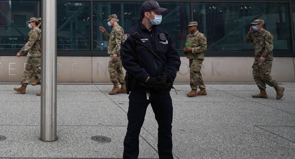 Los miembros de la Guardia Nacional del Ejército de EE.UU. caminan frente a un oficial de policía con una máscara afuera del Centro Jacob K. Javits en Nueva York. (Bryan R. Smith / AFP / Referencial).