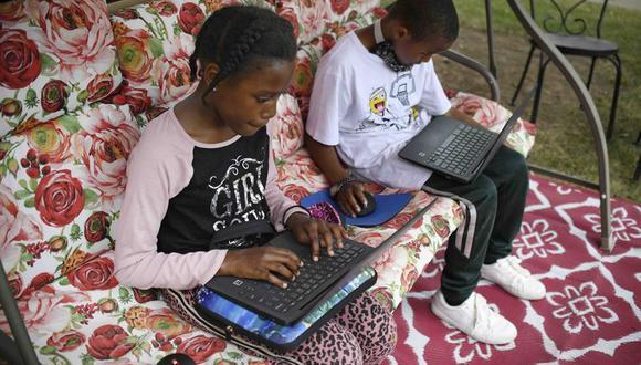 En esta imagen del 5 de junio de 2020 Sammiayah Thompson, estudiante de cuarto grado, y su hermano Nehemiah Thompson, quien cursa el tercer grado, trabajan desde su jardín en laptops que les entregó su sistema escolar para el aprendizaje remoto en Hartford, Connecticut. (AP Foto/Jessica Hill, Archivo).