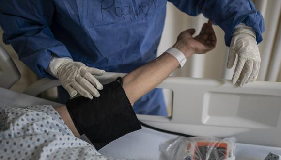 Un trabajador de salud mide la presión arterial en un paciente de COVID-19 internado en un hospital de México. (Foto: PEDRO PARDO / AFP)