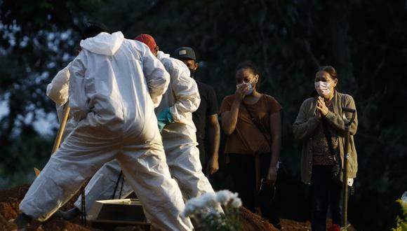 La gente llora mientras un familiar es enterrado en el cementerio de Vila Formosa en Sao Paulo, Brasil, el 17 de abril de 2021. (Foto de Miguel SCHINCARIOL / AFP).