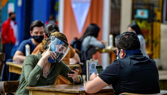 Un grupo de personas usa mascarillas y protectores faciales durante una prueba piloto de la apertura de un restaurante en la zona turística de Chorro de Quevedo, en Bogotá, el 1 de septiembre de 2020. (Foto de Juan BARRETO / AFP).