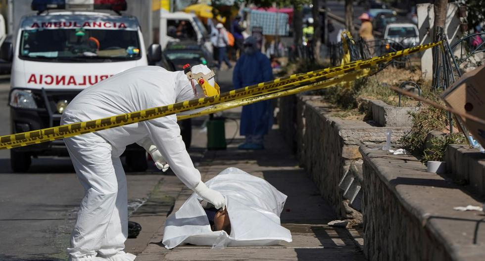 Un trabajador sanitarios del Instituto de Investigaciones Forenses recoge un cadáver que yacía el lunes en una de las calles de Cochabamba. (Foto: Danilo Balderrama / Reuters)