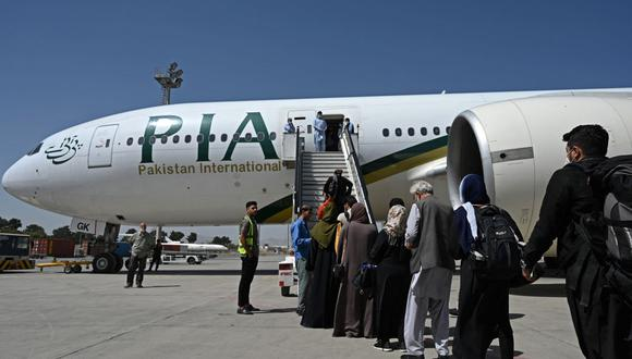 Los pasajeros abordan un vuelo de Pakistan International Airlines (PIA), el primer vuelo internacional comercial desde que los talibanes recuperaron el poder en Afganistán. (Aamir QURESHI / AFP).
