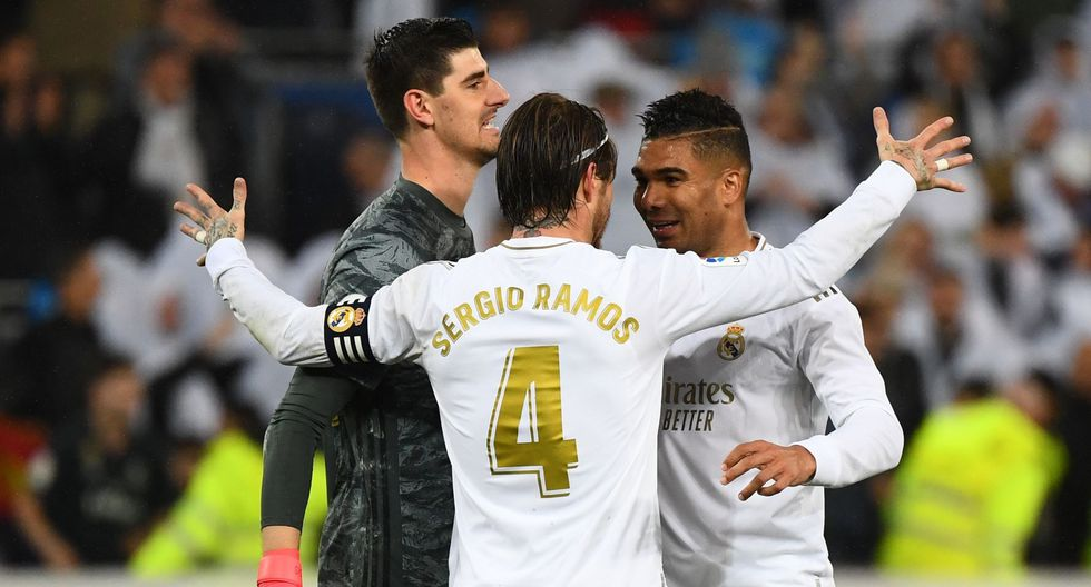 (L-R) Real Madrid's Belgian goalkeeper Thibaut Courtois, Real Madrid's Spanish defender Sergio Ramos and Real Madrid's Brazilian midfielder Casemiro celebrate at the end of the Spanish League football match between Real Madrid and Barcelona at the Santiago Bernabeu stadium in Madrid on March 1, 2020. / AFP / GABRIEL BOUYS