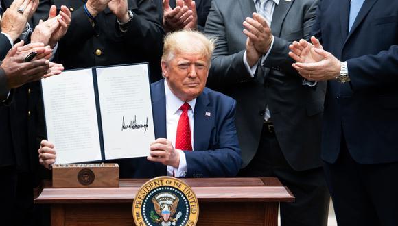 El presidente de Estados Unidos, Donald Trump, mostrando la firma. (Foto: AFP).