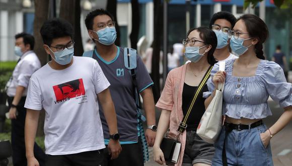 Las personas que usan máscaras faciales para ayudar a protegerse contra el coronavirus mientras caminan en Beijing. (Foto: AP / Andy Wong)